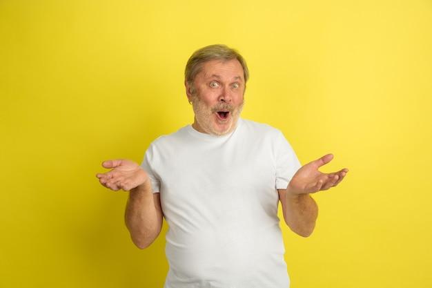 黄色で魅力的なジェスチャーをする白人男性