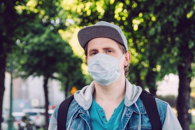 Caucasian man in medical mask walks through the park in summer