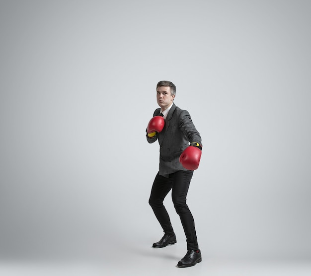 Caucasian man in office clothes boxing with two red gloves on grey background.