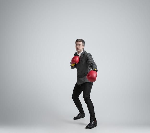 Uomo caucasico in abiti da ufficio boxe con due guanti rossi su sfondo grigio.