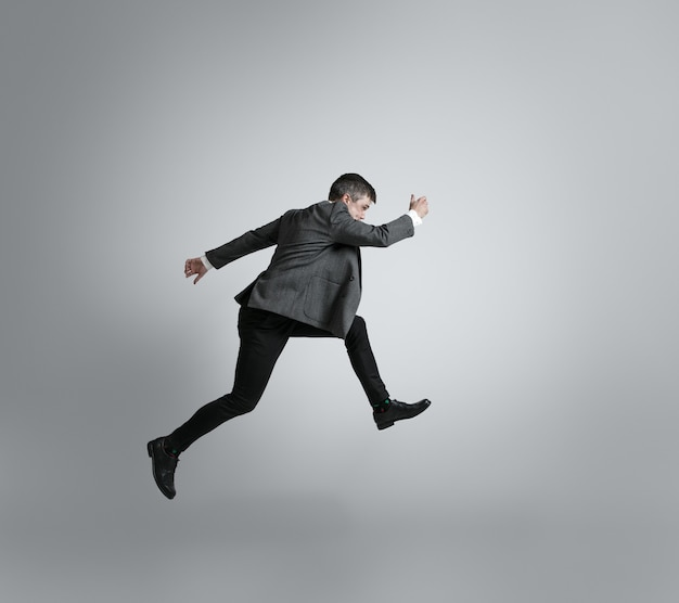 Caucasian man in office clothes running isolated on grey  wall