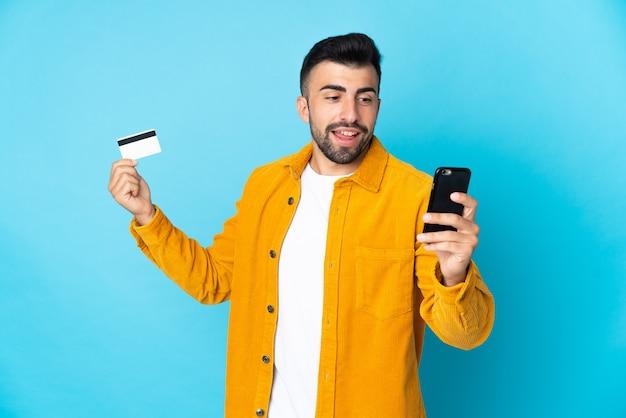 Кавказский мужчина над синим покупает мобильный телефон с помощью кредитной карты