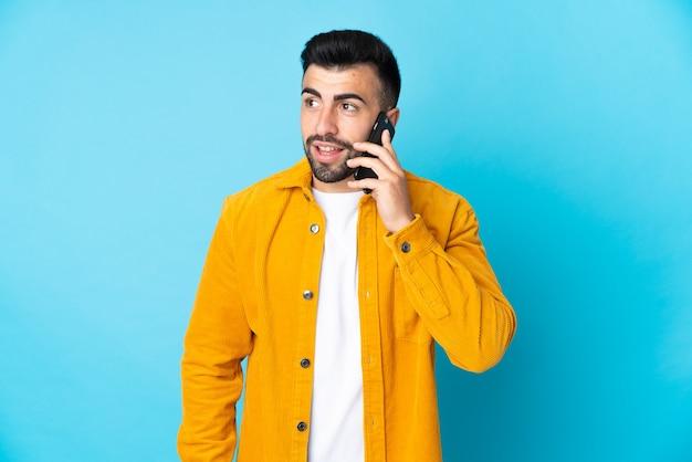 Кавказский мужчина на изолированном синем фоне разговаривает по мобильному телефону с кем-то