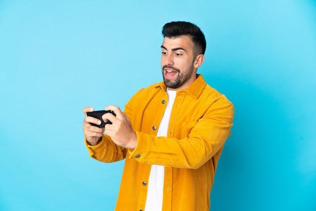 Кавказский человек на изолированном синем фоне играет с мобильным телефоном
