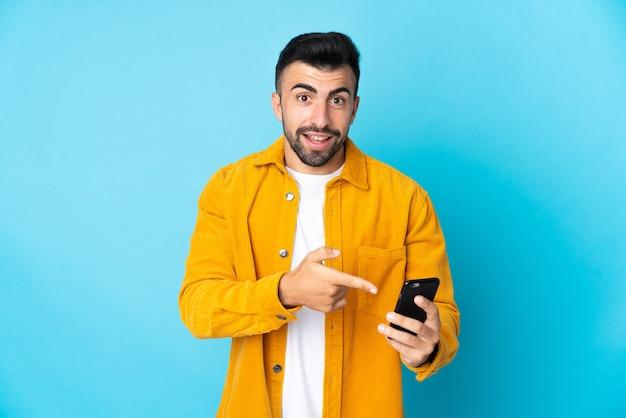 휴대 전화를 사용하고 그것을 가리키는 격리 된 파란색 배경 위에 백인 남자