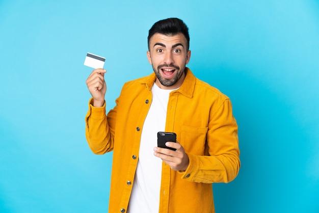 Кавказский мужчина над изолированной синей стеной покупает с помощью мобильного телефона и держит кредитную карту с удивленным выражением лица