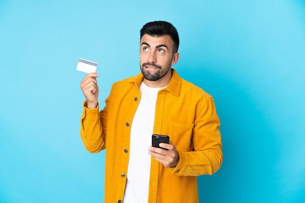 Кавказский человек над изолированной синей стеной покупает с мобильного с помощью кредитной карты, думая