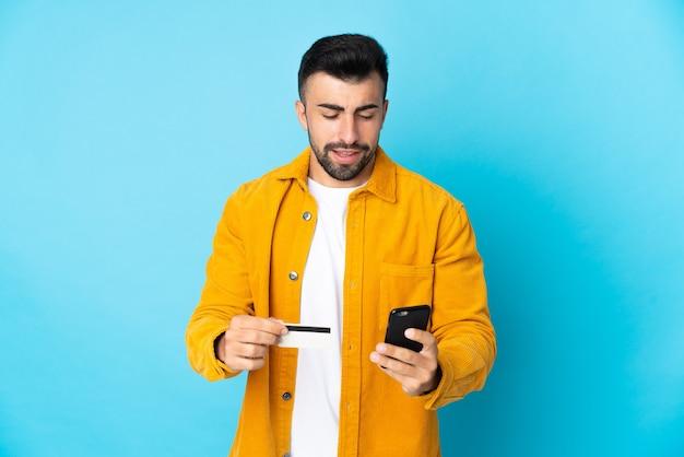 Кавказский мужчина над изолированной синей стеной покупает мобильный телефон с помощью кредитной карты