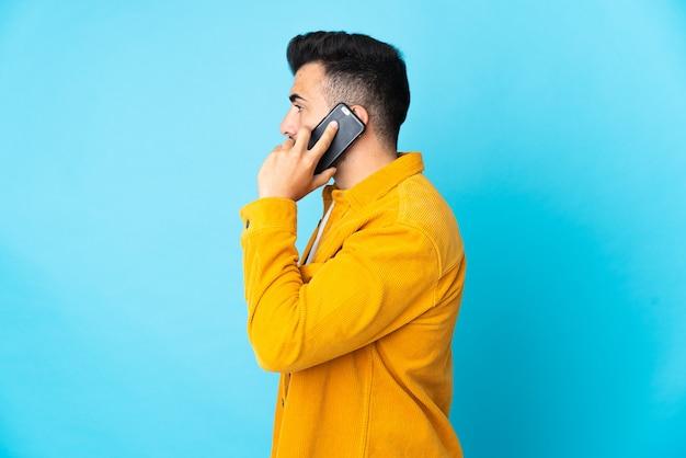 누군가와 휴대 전화로 대화를 유지하는 고립 된 파란색 벽 위에 백인 남자