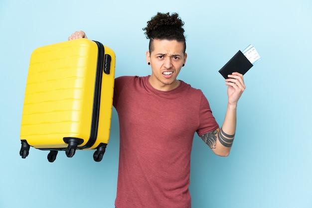 スーツケースとパスポートで休暇中に不幸な孤立した青い壁の上の白人男性