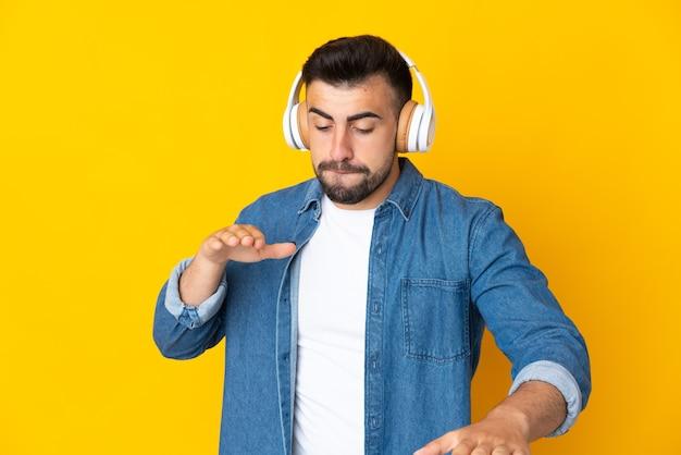 Кавказский человек на изолированном желтом фоне слушает музыку и танцует