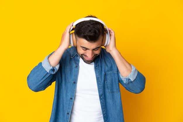 孤立した黄色の背景の上の白人男性が音楽を聴いています