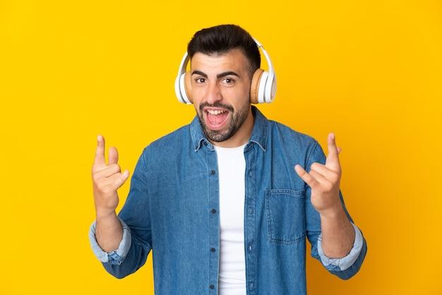ロックジェスチャーを作る孤立した黄色のリスニング音楽上の白人男性