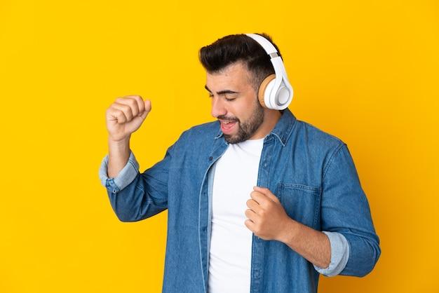Кавказский мужчина над изолированной желтой стеной слушает музыку и танцует