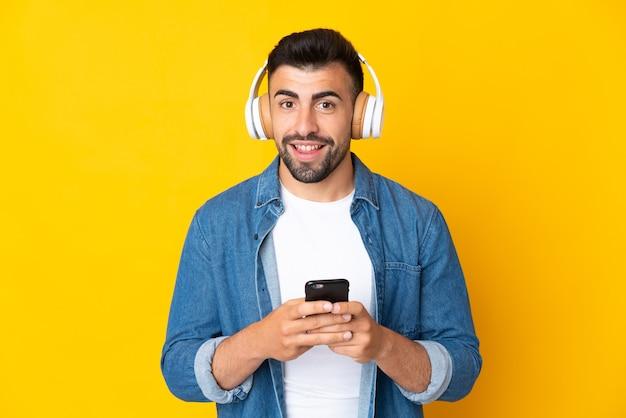 Кавказский мужчина над изолированной желтой стеной слушает музыку с помощью мобильного телефона и смотрит вперед