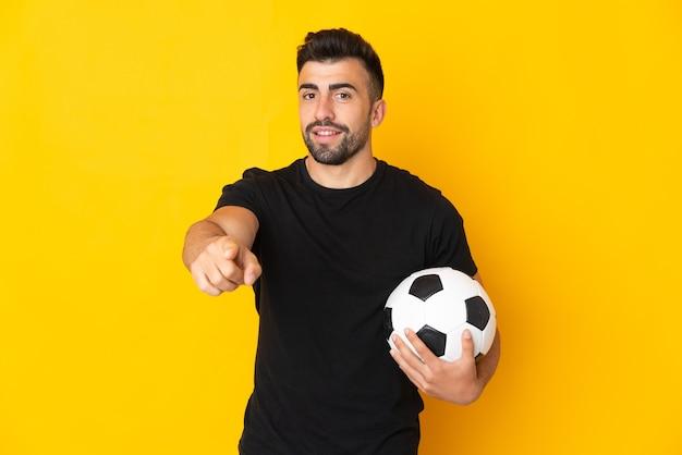 Кавказский человек над изолированным желтым с футбольным мячом и указывая вперед