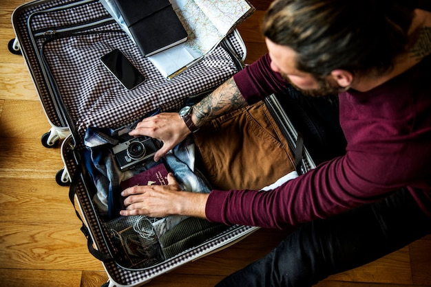 Caucasian man packing luggage for a trip