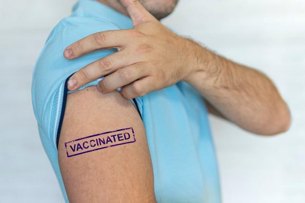 백인 남자, 파란색 스탬프를 가진 환자가 손에 예방 접종을 받았습니다. covid-19 코로나바이러스, 독감, 전염병에 대한 예방 접종의 개념. 주입. 전 세계 인구에 대한 의무적 인 대량 예방 접종