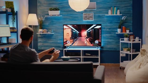 Uomo caucasico che gioca a giochi d'azione sulla console della tv