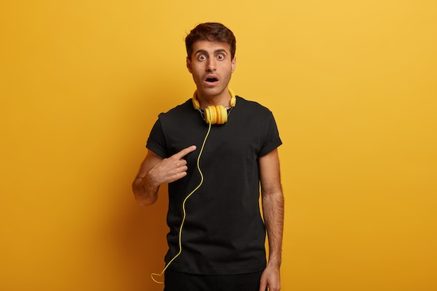 Caucasian man points at himself, feels shocked to be picked, keeps mouth wide opened, uses headphones for listening radio online, isolated on yellow wall