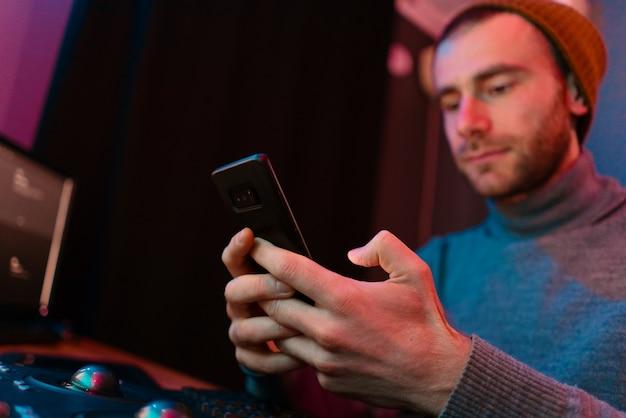 Caucasian man portrait on gradient studio background in neon light using smartphone while siting in his dark studio