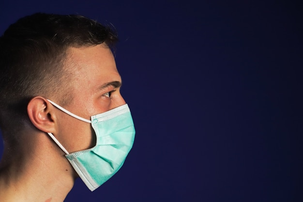 Caucasian man portrait in a medical gauze mask on dark blue background. covid-19 concept.
