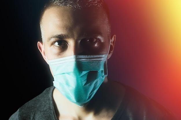 Caucasian man portrait in a medical gauze mask on dark blue background virus covid19 prevention