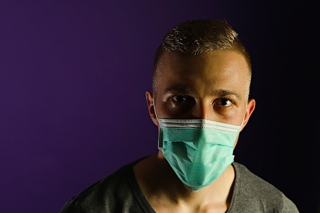 Caucasian man portrait in a medical gauze mask on dark blue background.