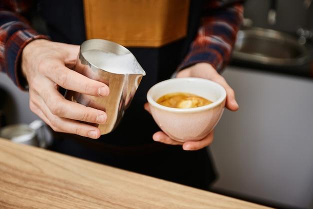 Caucasian man pouring hot milk in coffee