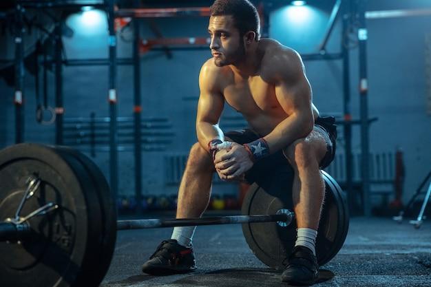 Кавказский мужчина занимается тяжелой атлетикой в тренажерном зале кавказская мужская спортивная модель позирует