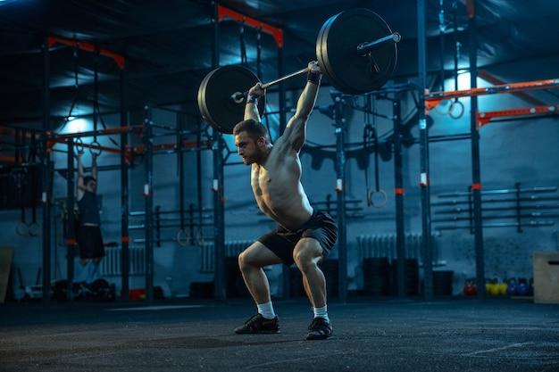 Кавказский человек занимается тяжелой атлетикой в тренажерном зале. кавказский мужчина спортивной модели тренируется со штангой, выглядит уверенным и сильным. бодибилдинг, здоровый образ жизни, движение, активность, концепция действий.