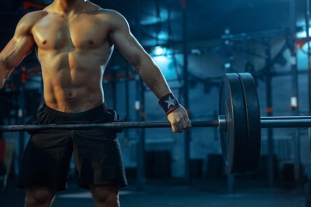 Кавказский человек занимается тяжелой атлетикой в тренажерном зале. кавказский мужчина спортивная модель тренируется со штангой, выглядит уверенно и сильно. бодибилдинг, здоровый образ жизни, движение, активность, концепция действий.