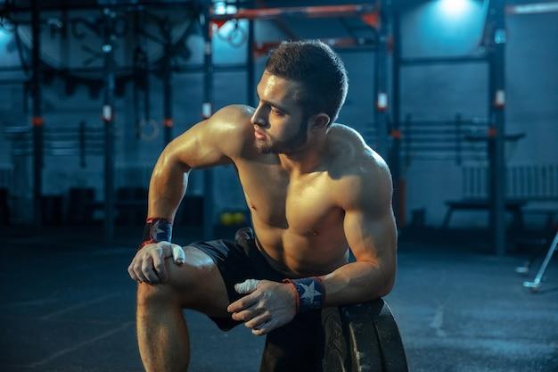Кавказский человек занимается тяжелой атлетикой в тренажерном зале