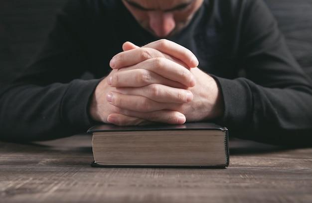 Кавказский мужчина молится в темной комнате.