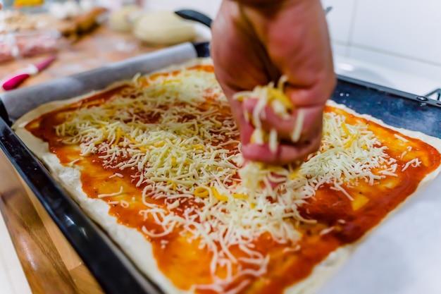白人男性がピザを準備し、チーズをトッピング