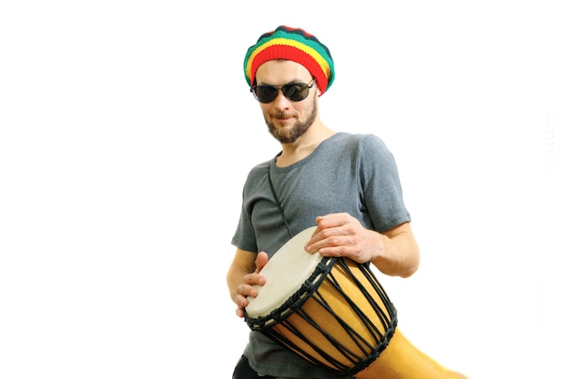Caucasian man in rasta hat sunglasses and grey tshirt on white background with djembe african drum