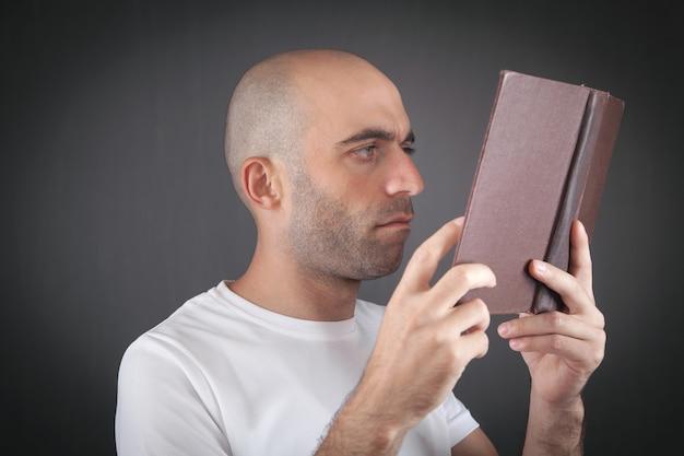 Caucasian man reading book in office.