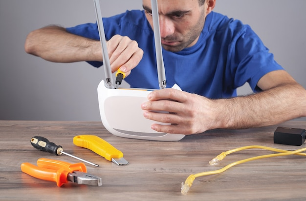 Кавказский мужчина ремонтирует маршрутизатор wi-fi.