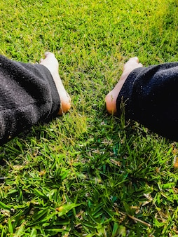 Кавказский мужчина отдыхает и смотрит себе в ноги, сидя на лужайке.