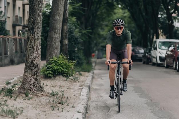 Caucasian man riding bike on asphalt road of city street