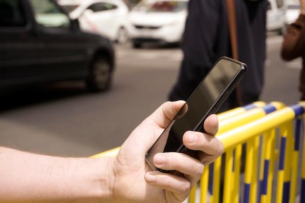 Рука кавказского человека в городе, держащая сотовый телефон с людьми не в фокусе на заднем плане