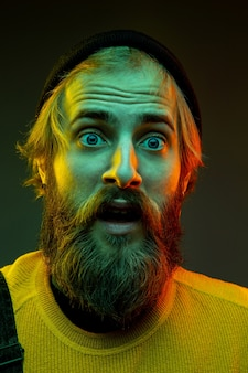 Caucasian man's portrait isolated on gradient studio background in neon light