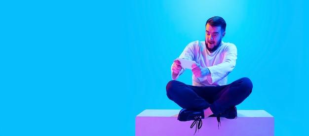 Портрет кавказского человека, изолированные на синем фоне студии в неоновом свете. красивая мужская модель. понятие человеческих эмоций, выражения лица, продаж, рекламы. copyspace для рекламы.