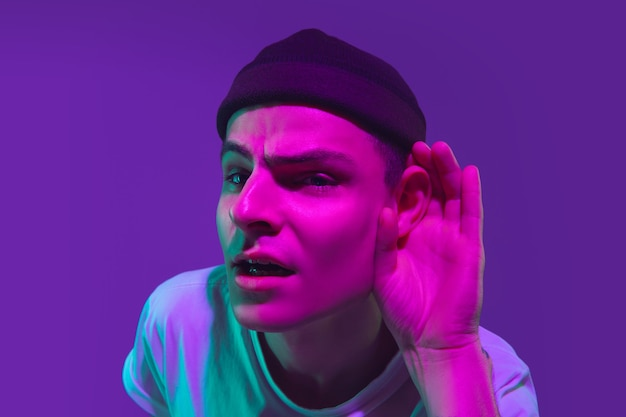 Портрет кавказского мужчины, изолированные на фиолетовом фоне студии в неоновом свете