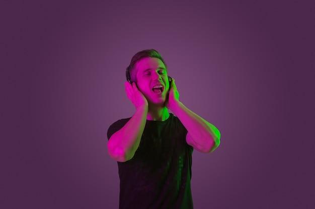 ネオンの光の紫色のスタジオで白人男性の肖像画。