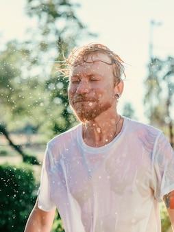 Кавказский мужчина качает головой с брызгами воды летняя веселая вечеринка отпуск эмоции удовольствие отн.