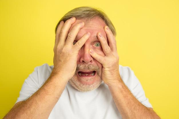 白人男性ショック、怖い、黄色で隔離の手で顔を覆う