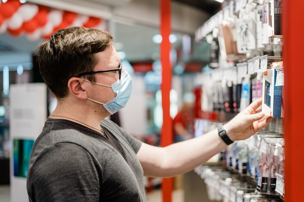 Caucasian man shopping for clothes with medical mask. new normal concept.