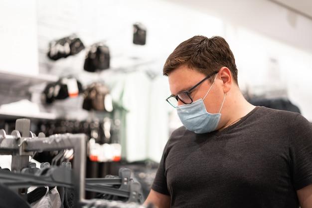 Кавказский человек, покупки для одежды с медицинской маской. новая нормальная концепция.