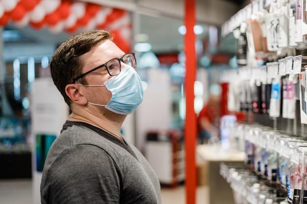 白人男性が医療用マスクで服の買い物。新しい通常のコンセプト。